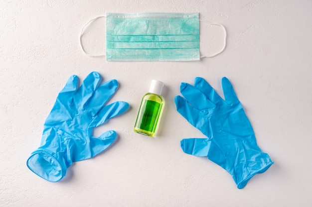 Luvas de borracha para máscara facial de garrafa de gel desinfetante para as mãos. conceito de prevenção e proteção à saúde do coronavirus covid19 vista superior Foto Premium
