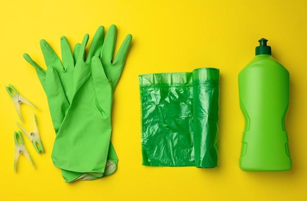 Luvas de borracha verde para limpeza, rolo de saco plástico para lixo e garrafa de plástico com detergente em fundo amarelo, conjunto