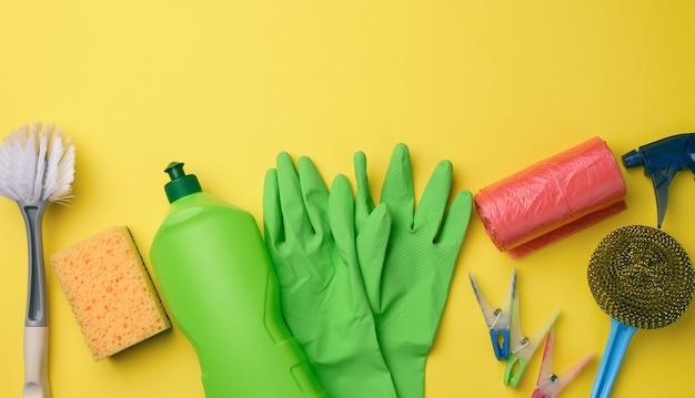 Luvas de borracha verdes para limpeza, lata de lixo vermelha, rolo de saco de plástico e garrafa de plástico com detergente, escova no fundo amarelo, conjunto, vista de cima