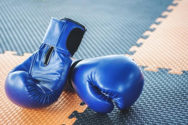 Luvas de boxe azuis estão no chão de borracha laranja e preto.