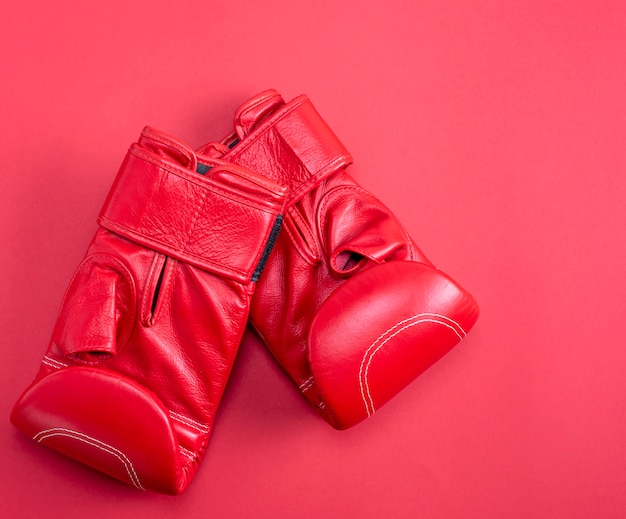 Luvas de boxe de couro esporte vermelho sobre um fundo vermelho
