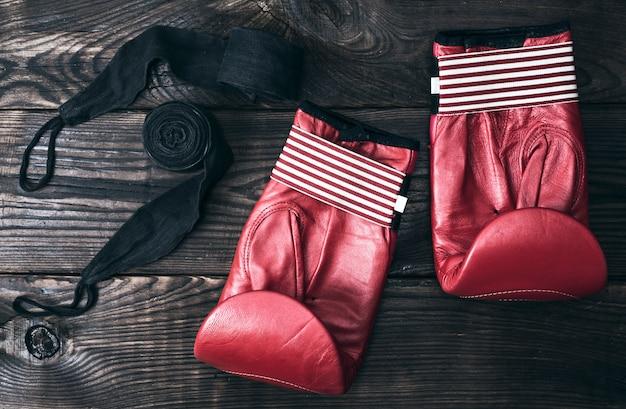 Luvas de boxe de couro vermelho e uma atadura elástica preta