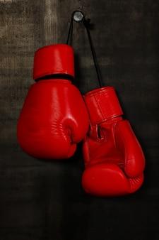 Luvas de boxe de couro vermelho pendurado na parede preta