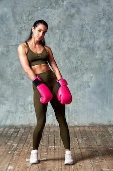 Luvas de boxe linda jovem perto da parede