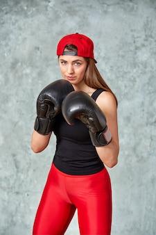 Luvas de boxe linda jovem perto da parede.