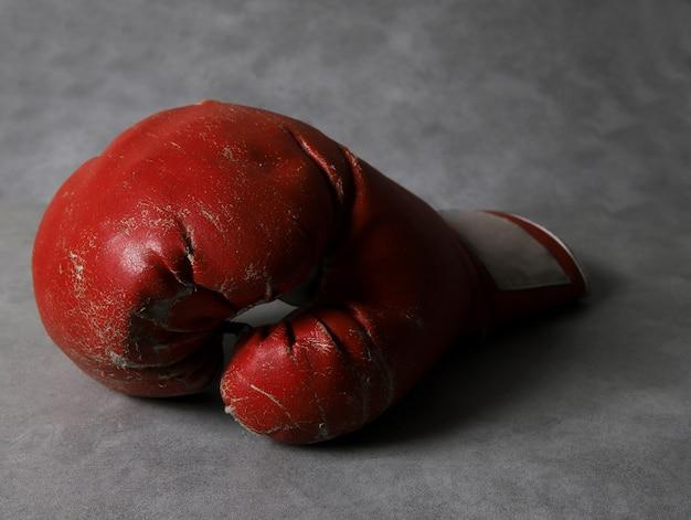 Luvas de boxe no chão do ginásio após o treino. fundo cinza de concreto grunge.