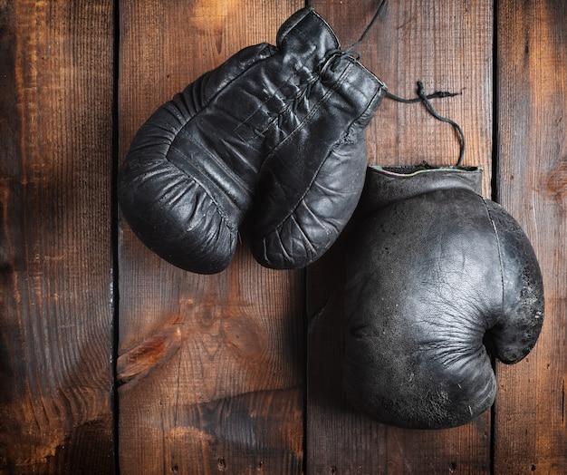 Luvas de boxe pretas muito velhas em madeira marrom