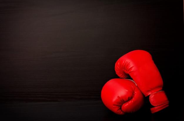Luvas de boxe vermelhas em uma mesa preta