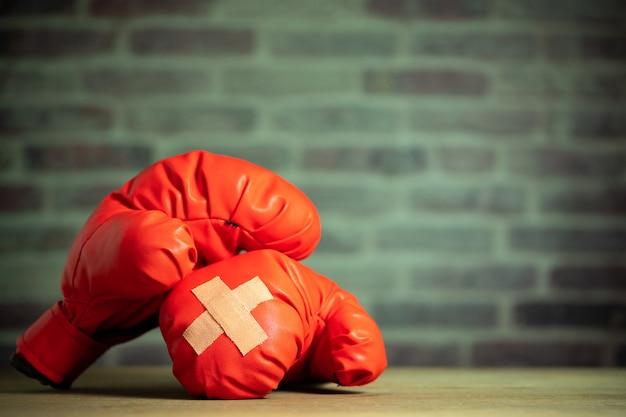 Luvas de boxe vermelhas na mesa de madeira e parede de tijolos no ginásio de esporte