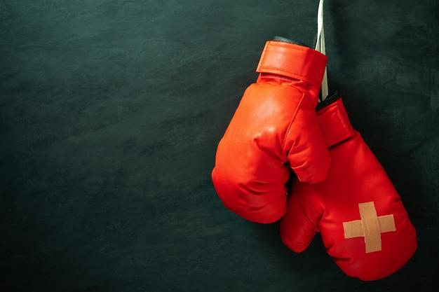 Luvas de boxe vermelhas penduradas na parede de cimento preto na escuridão com iluminação