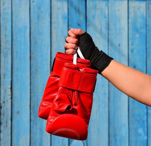 Luvas de boxe vermelhas pendurado em uma corda na mão de uma mulher