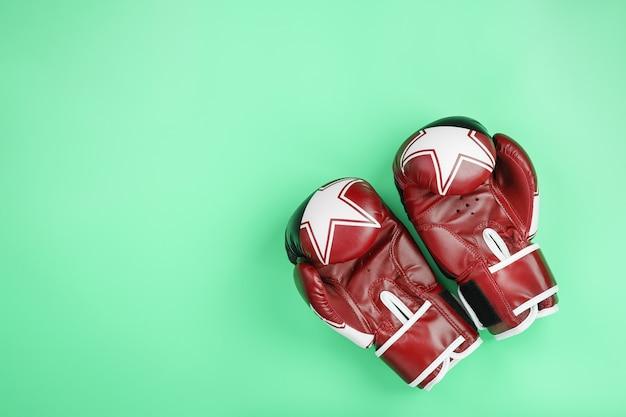 Luvas de boxe vermelhas sobre fundo verde, espaço livre