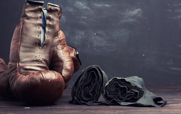 Luvas de boxe vintage de couro marrom e bandagem elástica preta para as mãos em um fundo preto