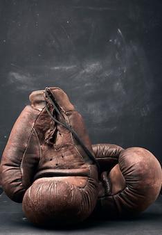 Luvas de boxe vintage de couro marrom em um fundo preto