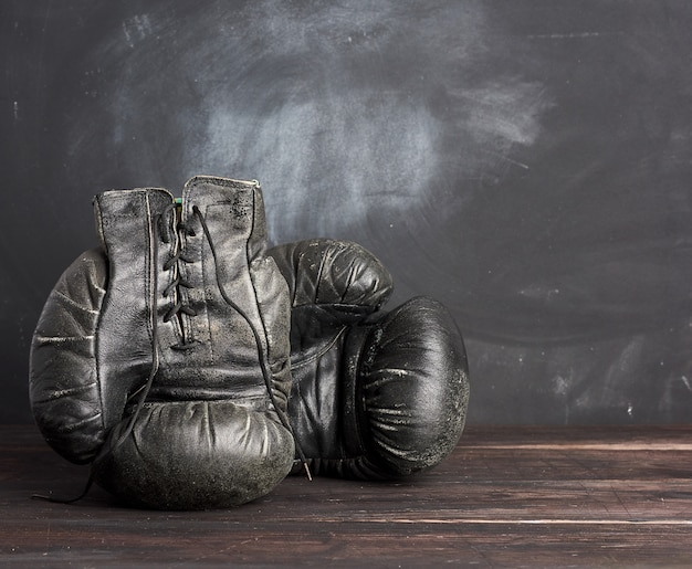 Luvas de boxe vintage de couro preto em um espaço preto