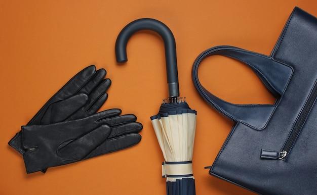 Luvas de couro, bolsa e guarda-chuva em marrom