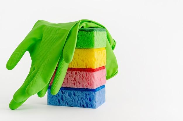 Luvas de látex e pilha de esponjas de limpeza isoladas no branco. copie o espaço