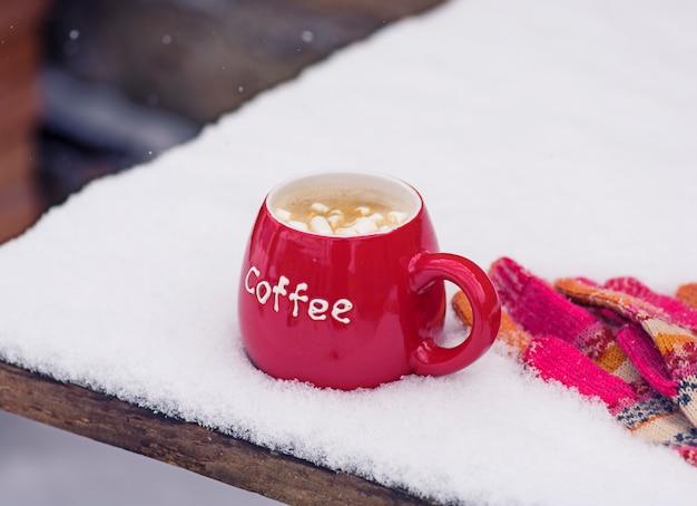 Luvas de malha e um copo vermelho com café