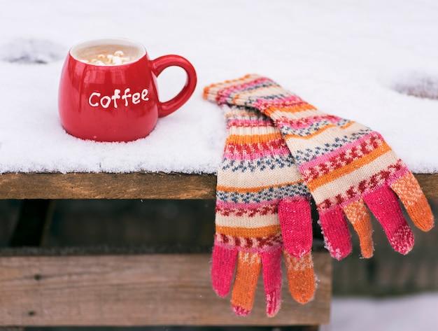Luvas de malha multi-coloridas e um copo vermelho com café