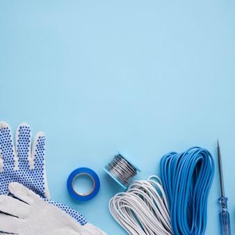 Luvas de mão; fita; bobina de fio metálico; fio e testador na superfície azul