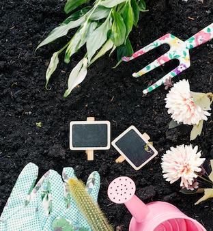 Luvas de mão; regador; flores; garfo de jardinagem; e plantas na sujeira preta