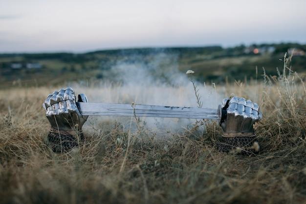 Luvas de metal e espada saindo do chão, ninguém, símbolo de grandes guerreiros no meio do campo