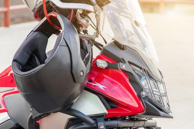 Luvas de motocicleta e capacete de segurança pendurado em um banco dianteiro de moto esporte para segurança