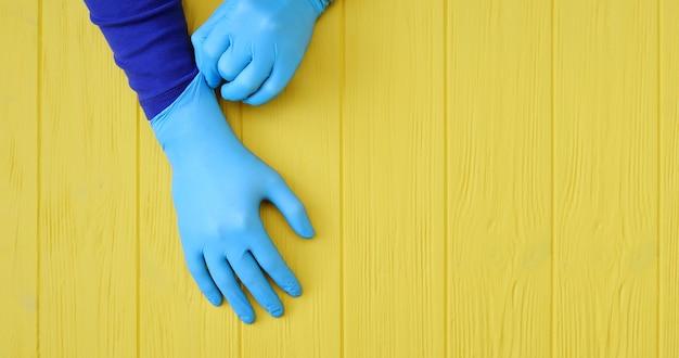 Luvas de nitrilo banner azul. mãos de um médico nas luvas de látex azuis sobre um fundo amarelo de madeira.