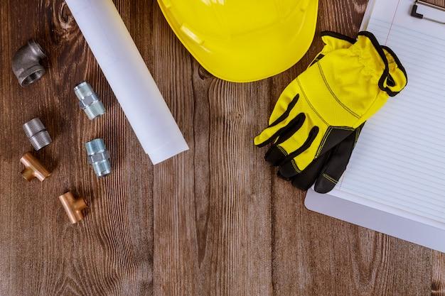 Luvas de proteção no capacete amarelo, tubos de cobre