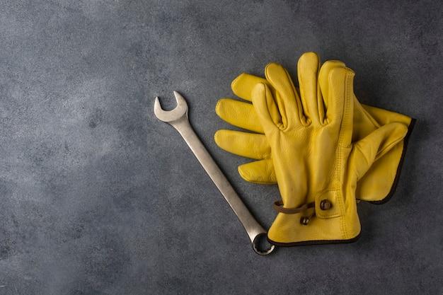 Luvas de trabalho amarelas e uma chave inglesa no chão de concreto