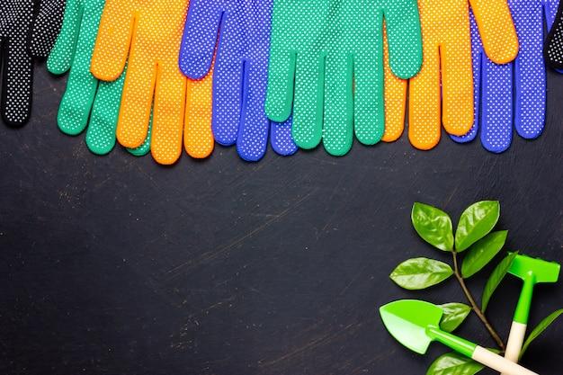 Luvas de trabalho e ferramentas de jardinagem em um fundo preto. o jardim fornece um lugar grátis