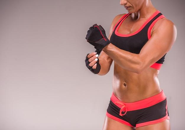 Luvas desgastando da mão do halterofilista fêmea para exercícios.
