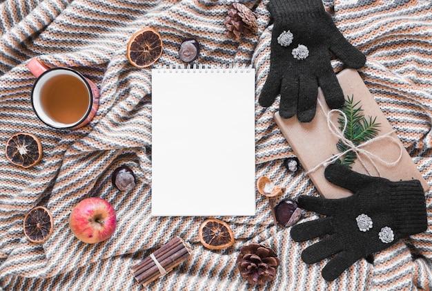 Luvas e chá perto de presente e notebook