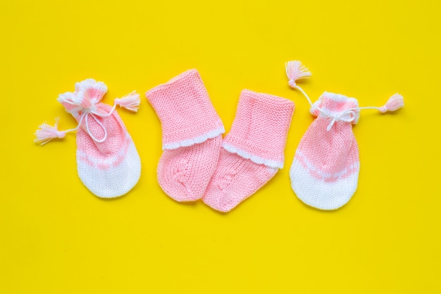Luvas e peúgas do bebê no fundo amarelo.
