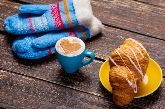 Luvas e xícara de café na mesa de madeira.
