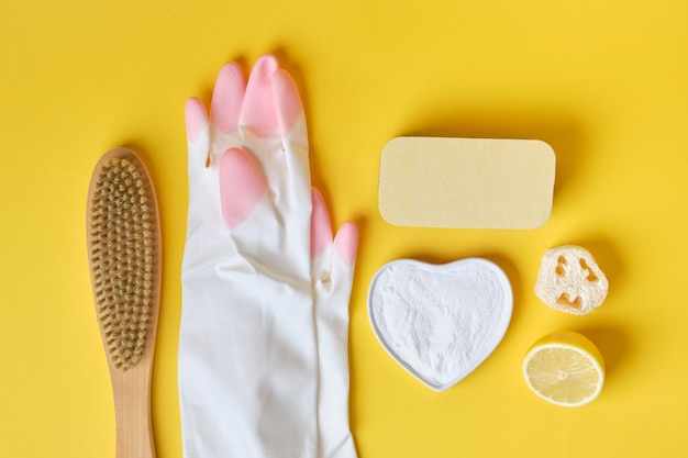 Luvas esponjas de refrigerante e escova no conceito de limpeza ecológica de fundo amarelo