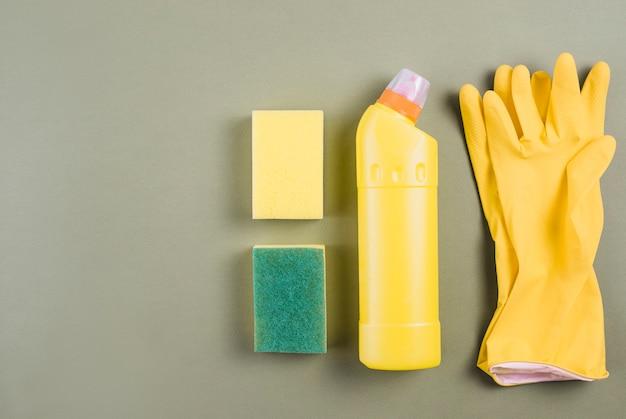 Luvas, frasco de detergente e esponja em fundo colorido