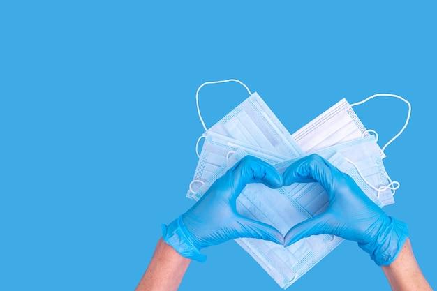 Luvas médicas azuis símbolo de mão em forma de coração em máscaras médicas de proteção em forma de coração em azul