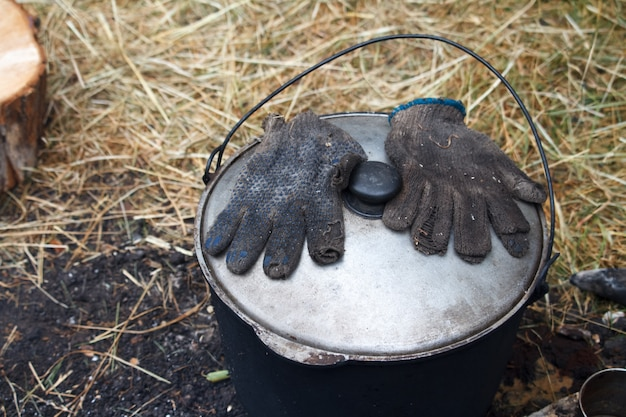 Luvas na fuligem estão na tampa de uma panela com comida pronta perto do fogo