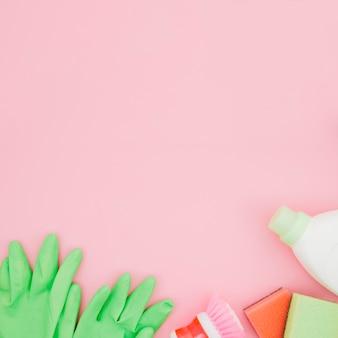 Luvas verdes; garrafa de spray; garrafas de esponja e detergente em pano de fundo amarelo