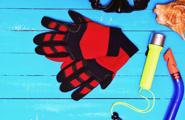 Luvas vermelhas para mergulho entre outros equipamentos esportivos