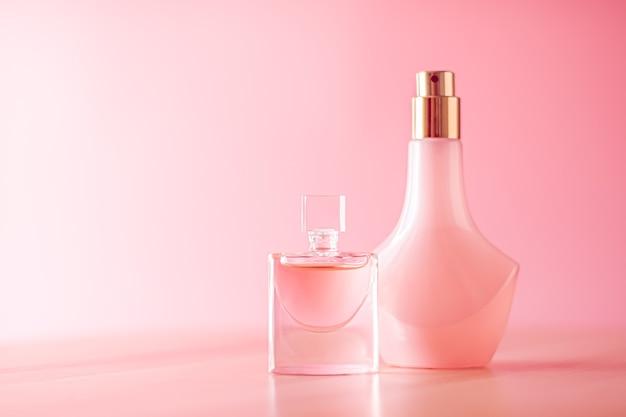 Luxo de frascos de perfume em fundo rosa