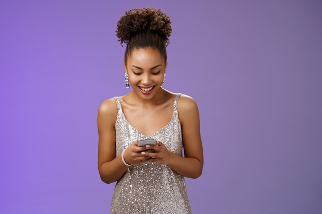 Luxuosa bonita elegante mulher afro-americana em um vestido de noite prateado segurando um smartphone, conversando com amigos que trocam mensagens de texto, sorrindo amplamente, esperando a namorada perto do telefone de comunicação de entrada do clube.