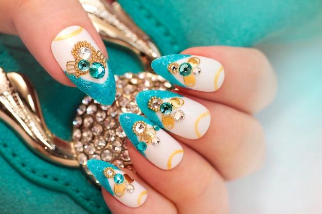 Luxuosa manicure francesa azul arenosa glamourosa com strass, boulongne e close up banhado a ouro das unhas femininas.
