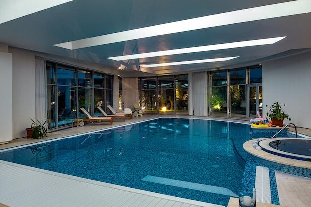 Luxuosa piscina coberta com banheira de hidromassagem e espreguiçadeiras em um cenário de um parque verde à noite.