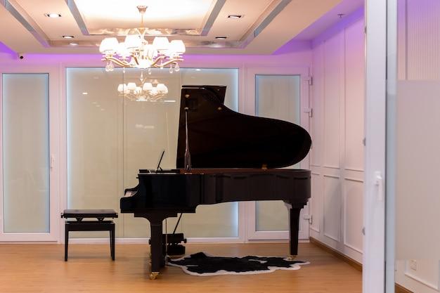 Luxuosa sala de música com piano de cauda e lustre com iluminação colorida.