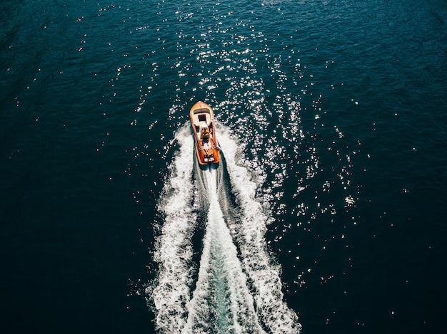 Luxuoso barco a motor de madeira com um par deitado correndo ao longo do mar