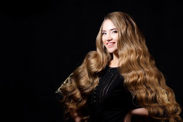 Luxuosos cachos dourados, retrato de uma jovem mulher bonita com cabelo bonito, fundo preto