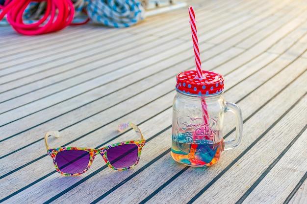 Luxuosos óculos roxos e uma caneca incomum com uma palha deitar no convés do iate durante a viagem.