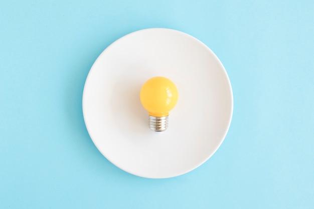 Luz amarela bulbo no prato branco sobre o pano de fundo azul
